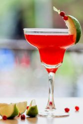 Scarlett O'hara Drink on table with limes and cranberries
