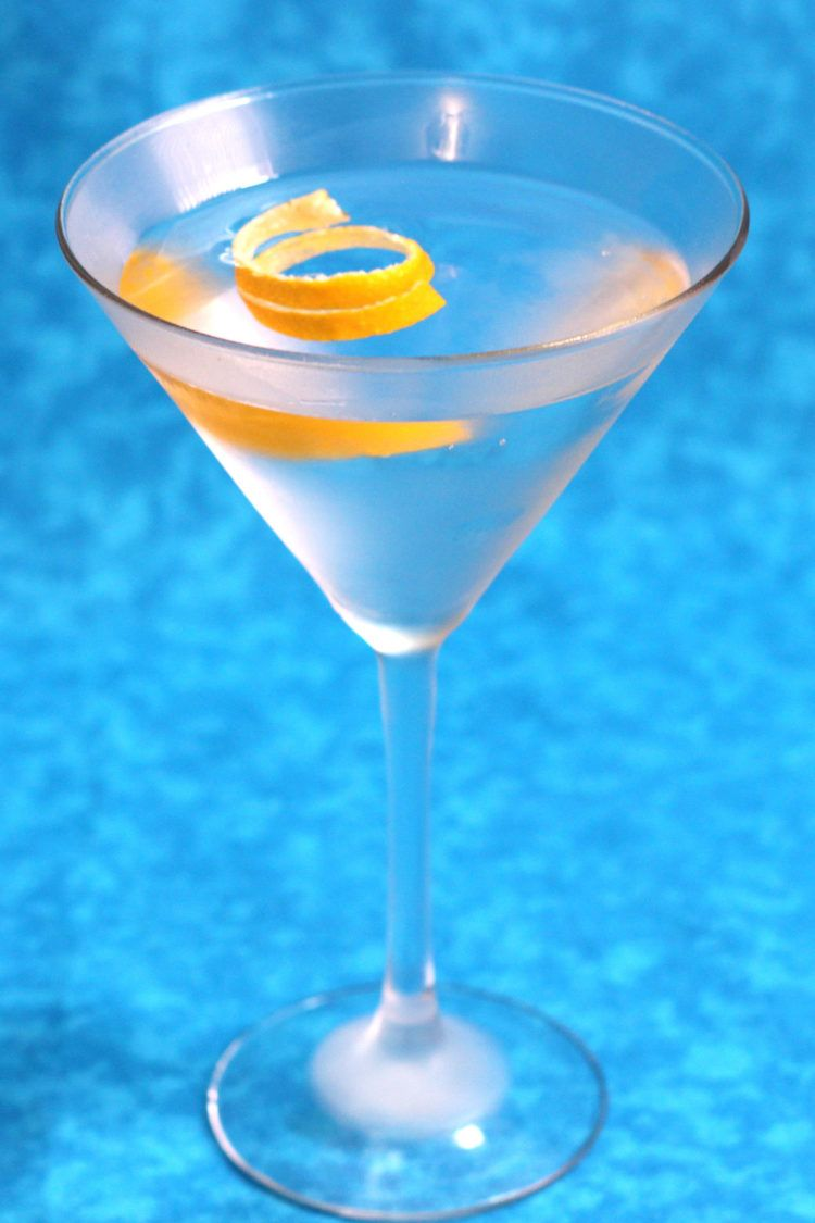 Gin martini with lemon twist against blue background