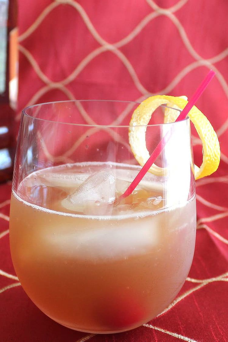 Amaretto Sour cocktail with lemon twist and cherry