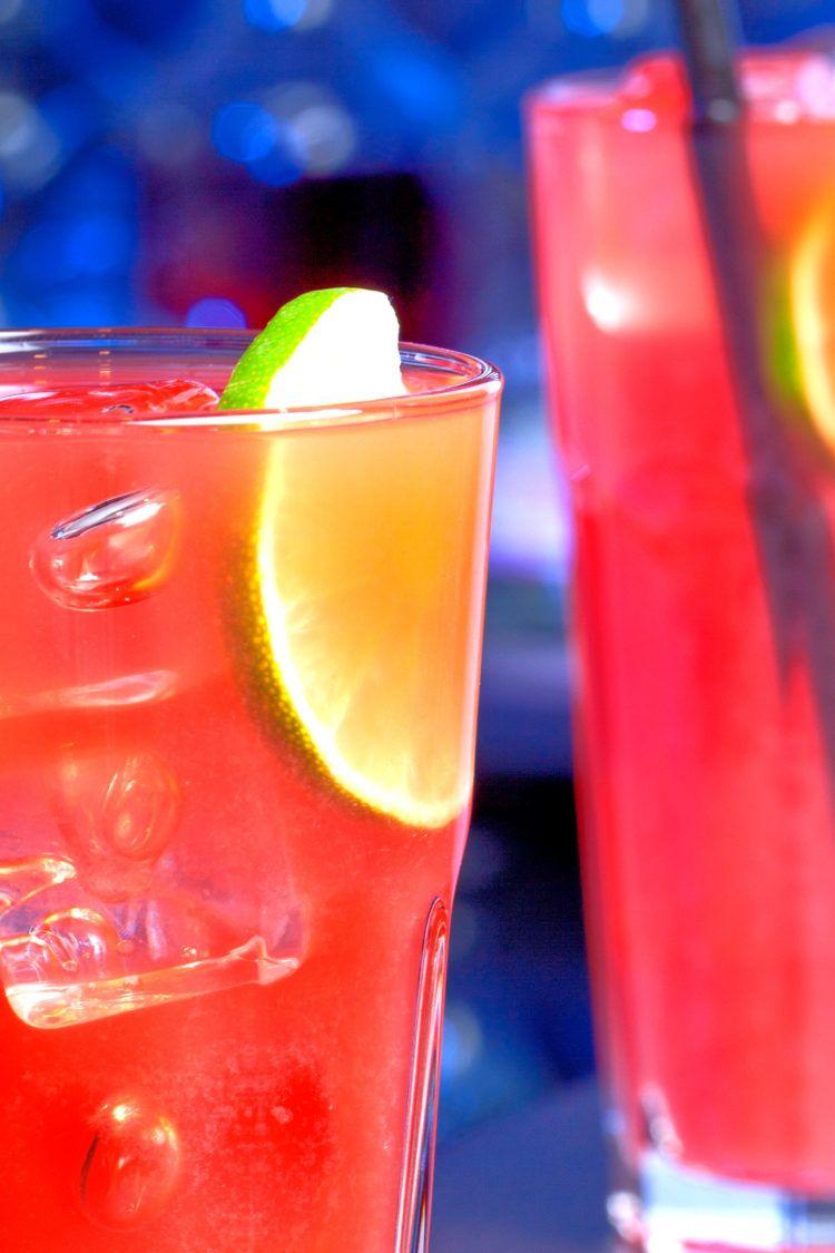 Sea Breeze drinks on bar against dark blue background
