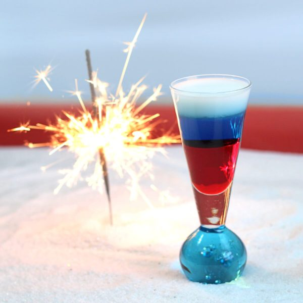 Fourth of July drink recipe with grenadine, blue curacao and cream, layered in a shot glass.