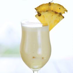 Pina Colada drink with pineapple wedges on table