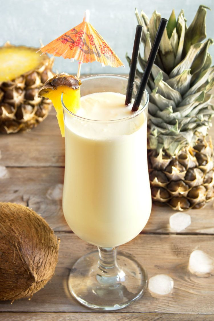 Pina Colada drink on table with pineapple and coconut