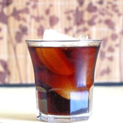 Jack and Coke drink on table in front of patterned background