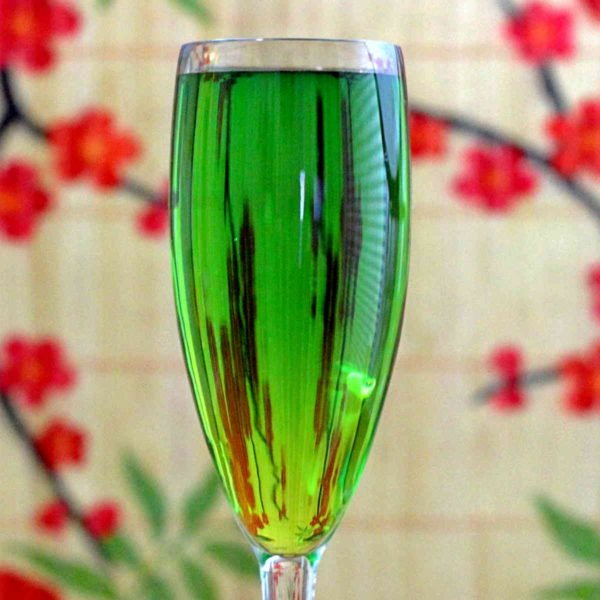 Bright green Jade cocktail against floral backdrop