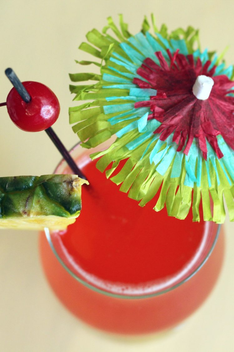 Overhead view of Zombie drink with pineapple and cherry with cocktail umbrella