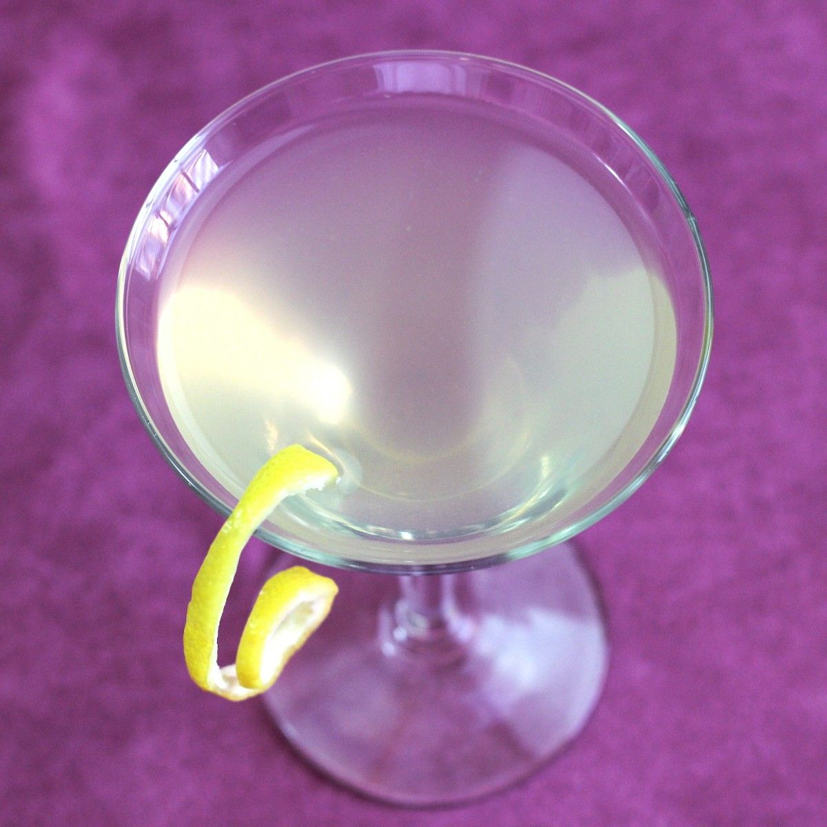 Cloudy clear cocktail in martini glass with lemon twist, dark blue background