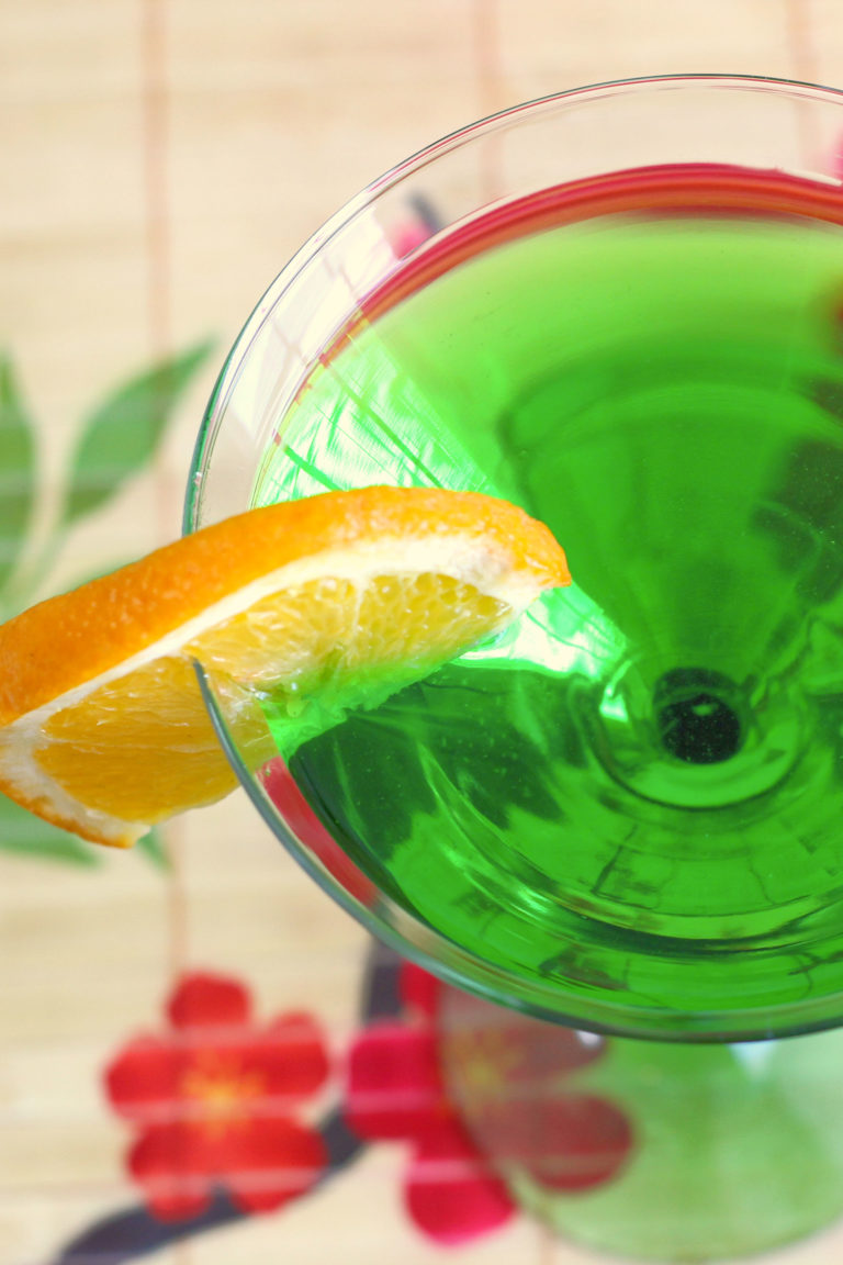 Overhead view of green drink with orange slice