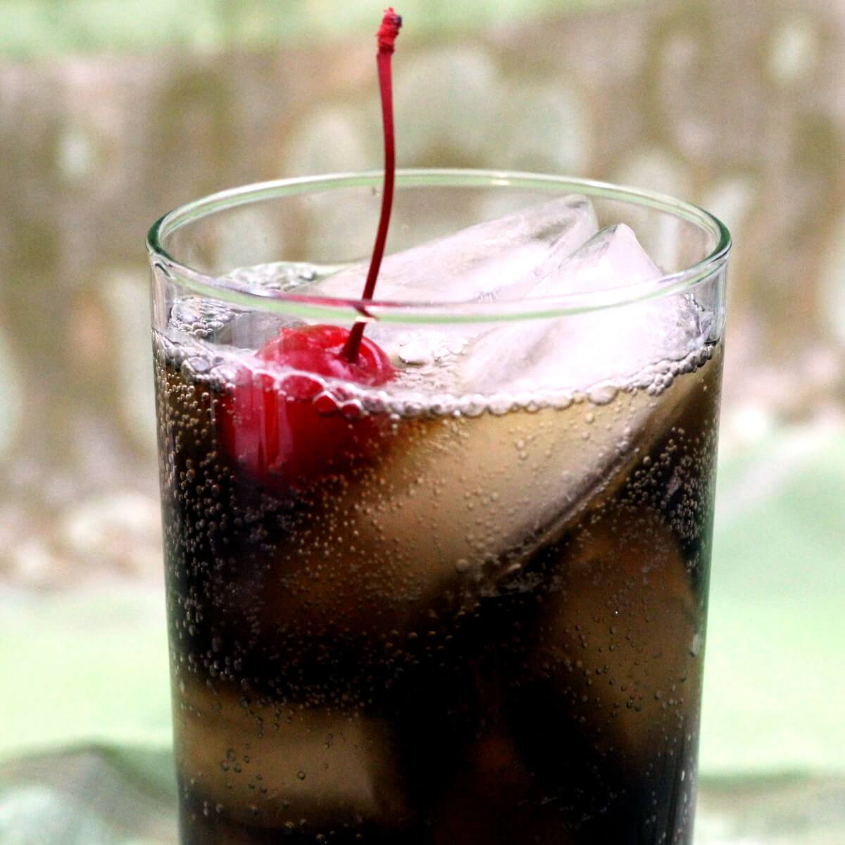 Dark carbonated drink over ice in tall glass with maraschino cherry