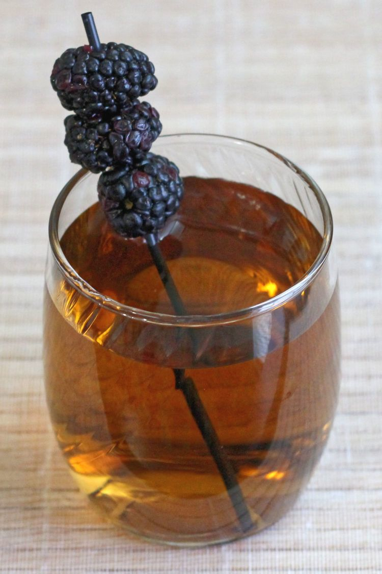Black cactus drink with blackberry garnish