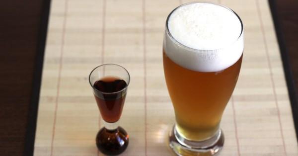 Boilermaker beer in Pilsner glass next to shot of whiskey
