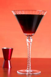 Dark brown Undertaker cocktail in tall martini glass next to red jigger