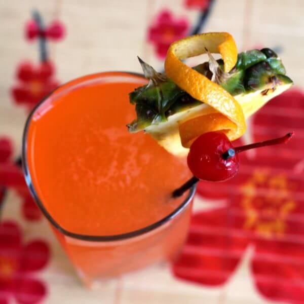 Reddish orange Hawaiian Hammer cocktail with pineapple, cherry and orange twist garnish