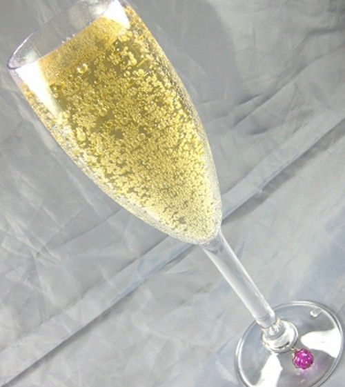 Bubbly golden cocktail in champagne flute with purple wine charm on glass stem, gray background