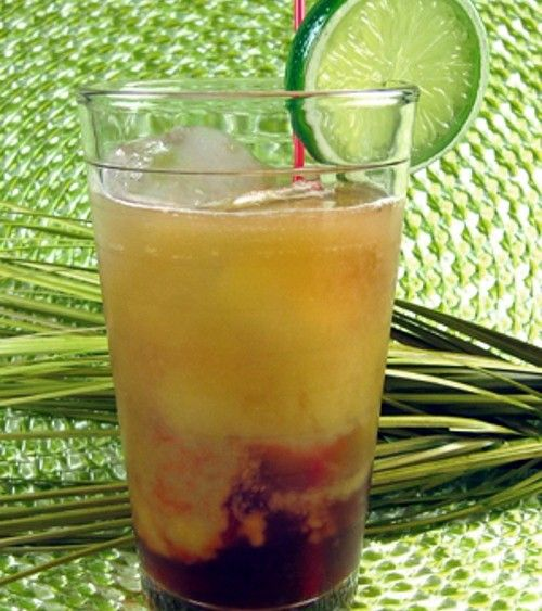 Cocktail with reddish-brown at bottom and orange on top, with straw and lime wheel