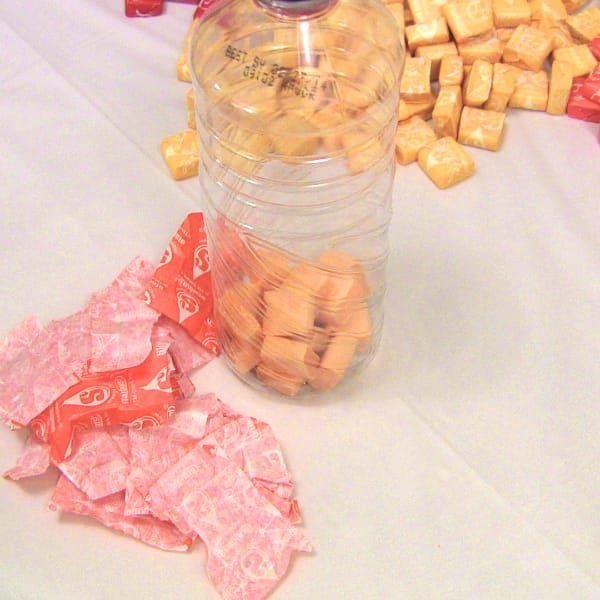 Closeup of orange starbursts in bottle with candy wrappers scattered beside bottle