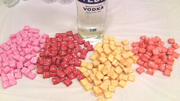 Piles of Starbursts separated into flavors with bottle of vodka in background