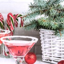 Two Christmas drinks garnished with candy canes and surrounded by Christmas decor