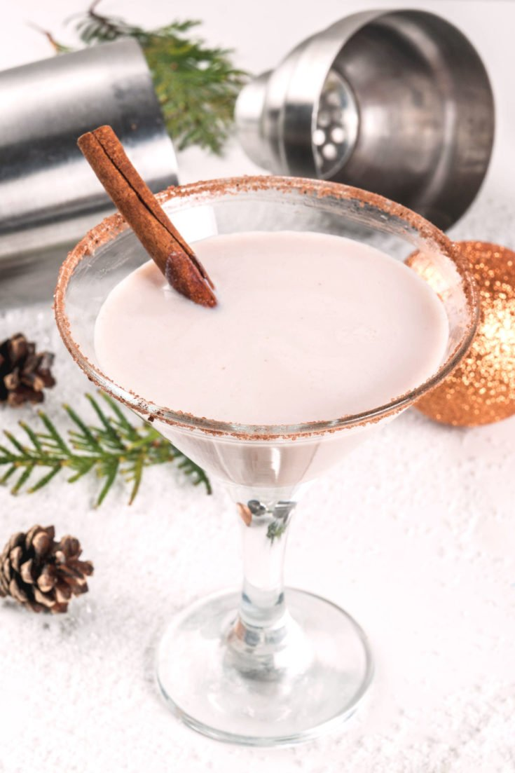 Eggnog Martini surrounded by Christmas decorations