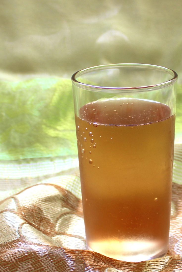 Golden brown cocktail against green cloth background