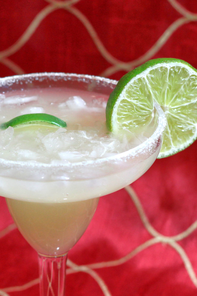 Beer Margarita with lime wheel against red fabric backdrop