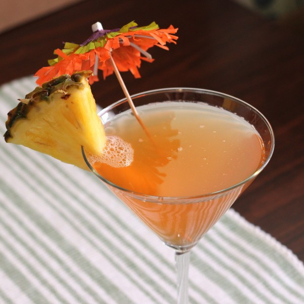 Side angle view of Ruby Relaxer drink with pineapple slice and cocktail umbrella