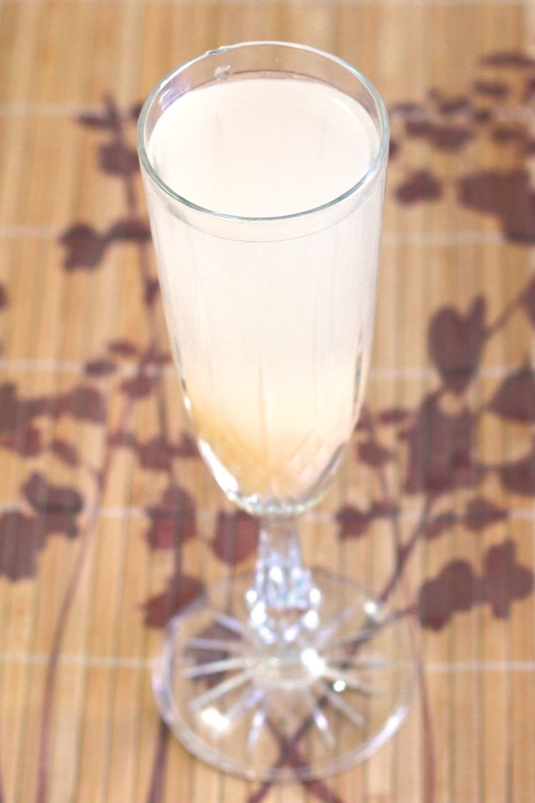 Bella Bellini cocktail in champagne flute on bamboo placemat
