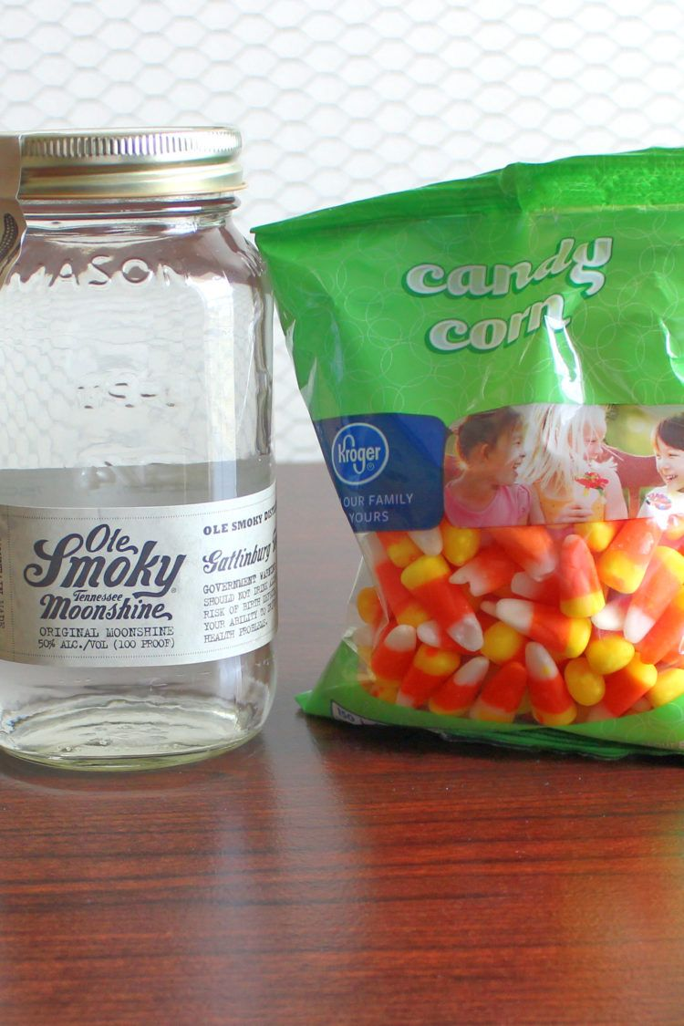 Bottle of moonshine next to bag of candy down