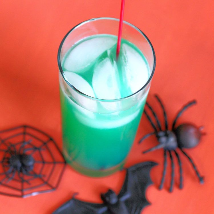Overhead view of Green Spooky Juice drink surrounded by toy spiders