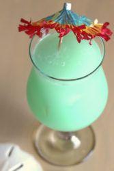 Greenish Hpnotiq Breeze cocktail with umbrella