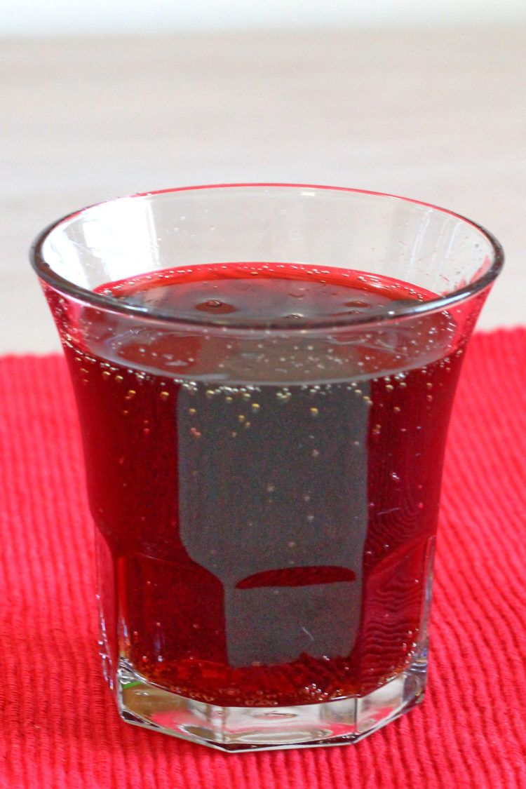 Cherry Coketail drink sitting on red placemat on table