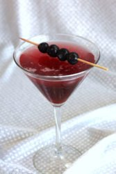 Berry Fusion Martini with blueberries on cocktail pick