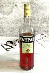 Bottle of Campari next to shot glass of same