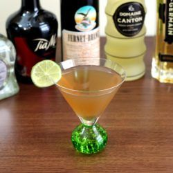 March Rain Cocktail with lime wheel in front of bottles of liquor