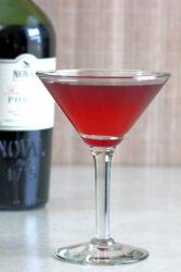 Crimson Cocktail in front of bottle of port