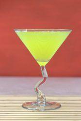 Bright yellow Algonquin Cocktail in front of dark orange background