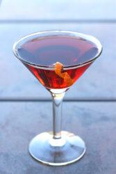 Boulevardier drink with orange twist on patio table