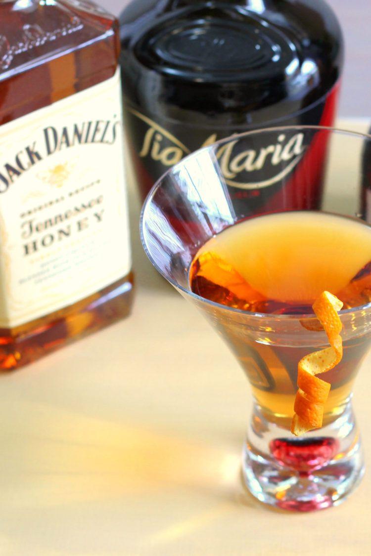 Jack's Grand Ball cocktail in front of liquor bottles
