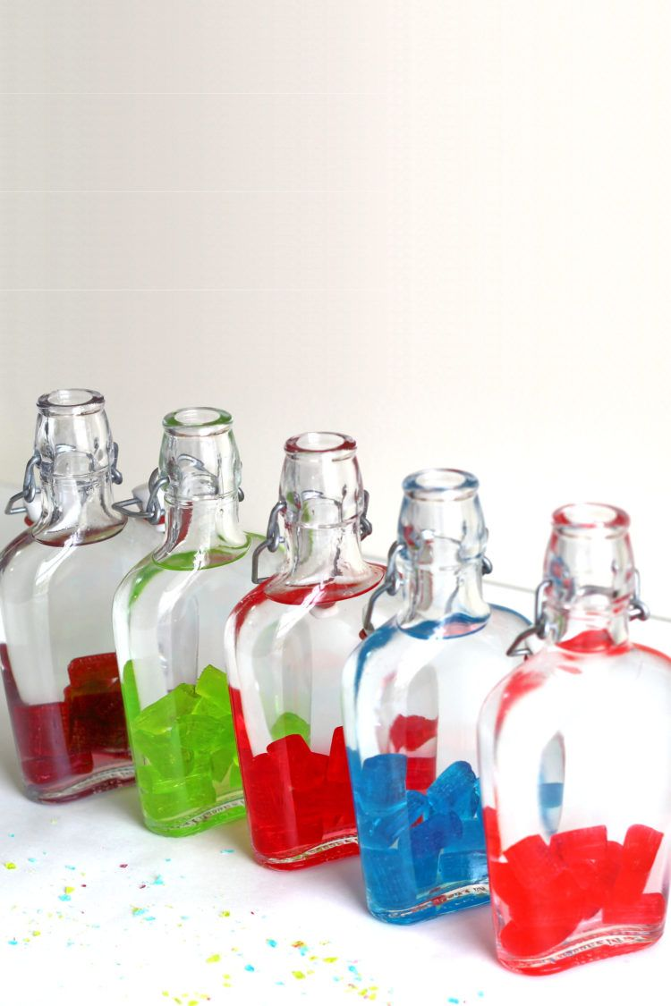Jolly Rancher candies in flasks with vodka poured over them