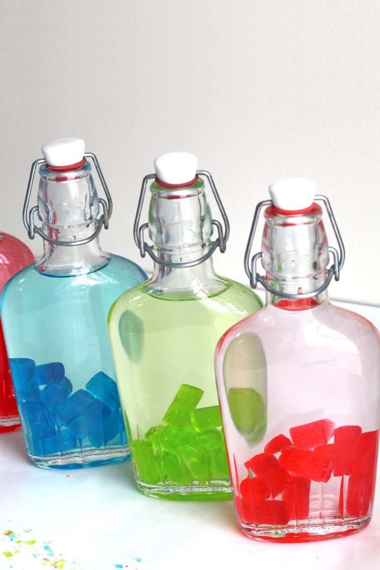 Closeup of Jolly Rancher candies starting to color the vodka in a flask