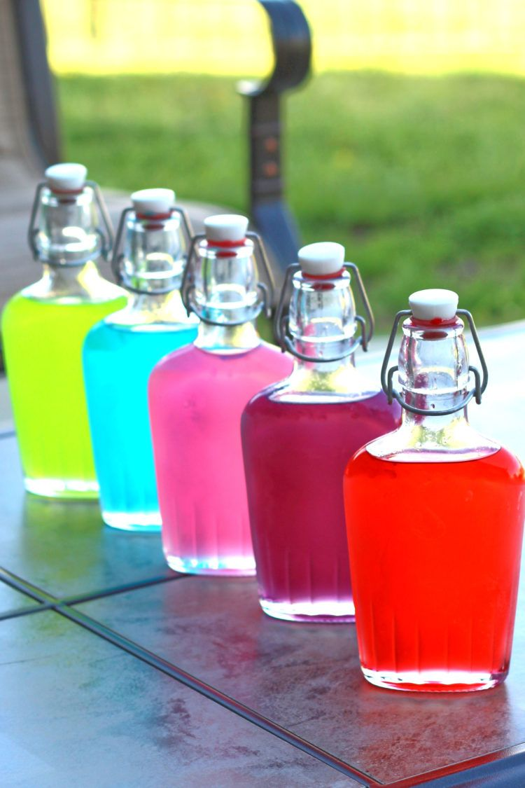 Jolly Rancher Vodka in flasks on a patio table