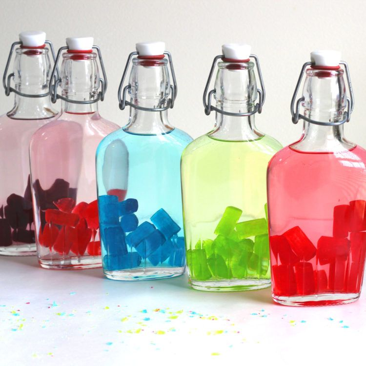 Full shot of Jolly Rancher candies starting to color the vodka in a flask