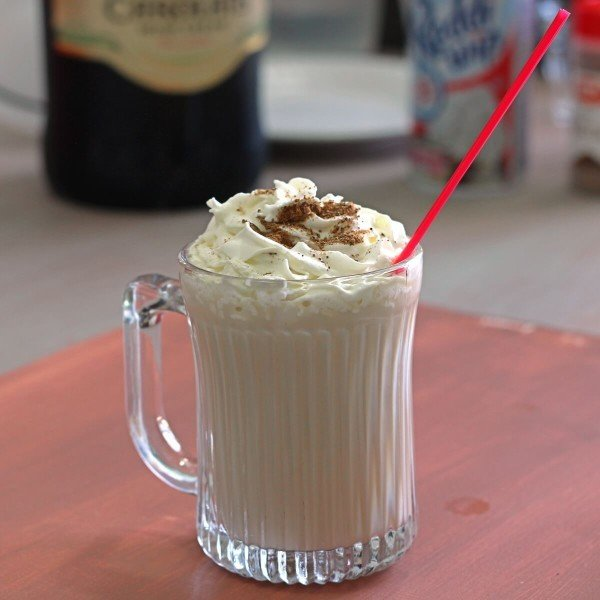 Butterscotch Coffee Cocktail in front of bottles of liquor and whipped cream