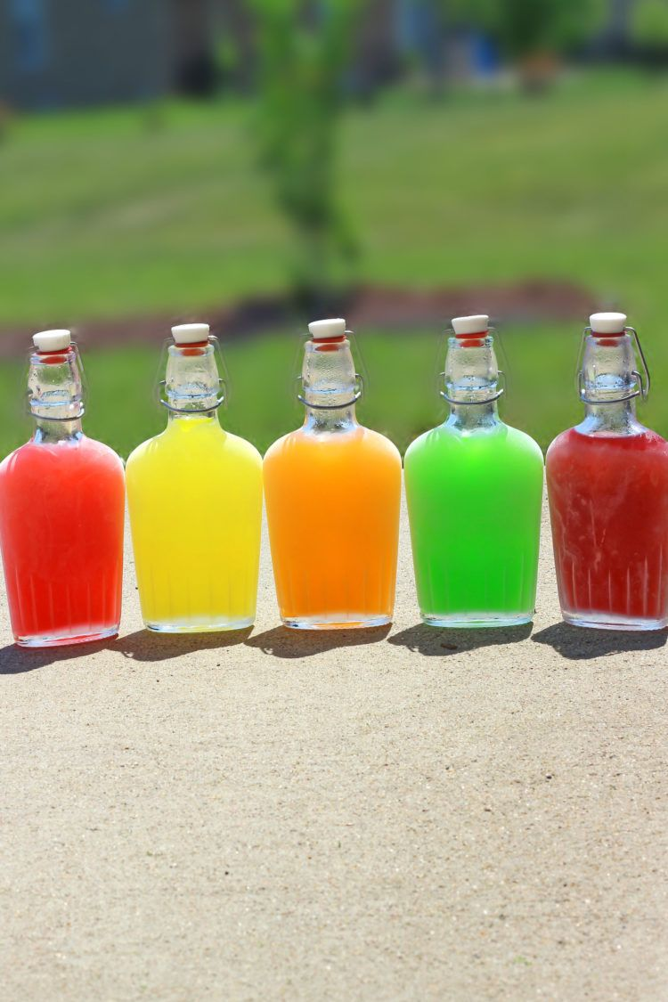 Chilled Skittles Vodka in flasks side by side on concrete patio