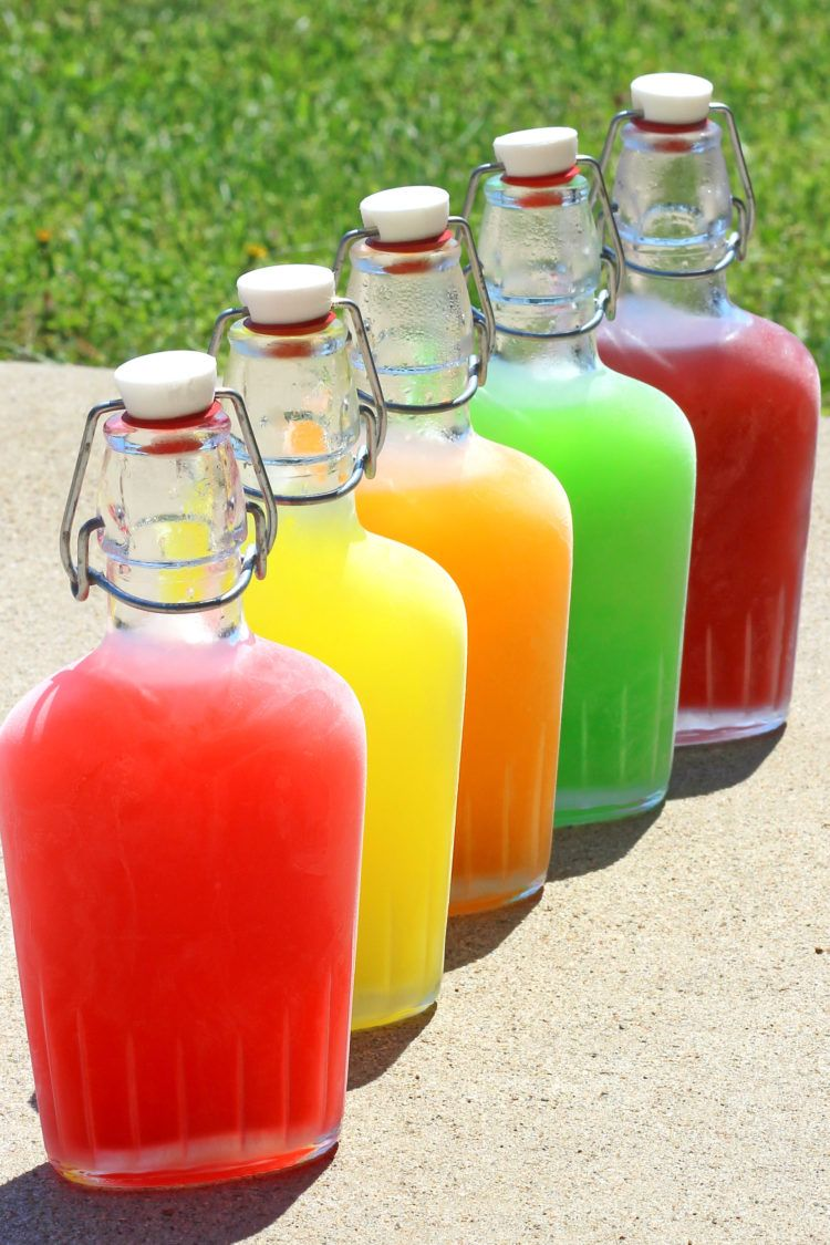 Chilled Skittles Vodka in flasks staggered one in front of another