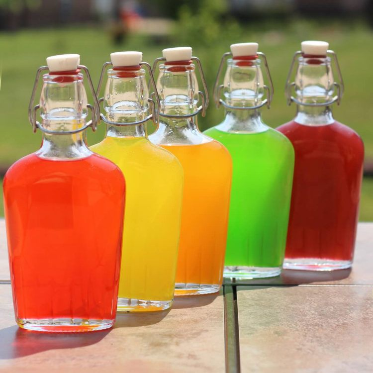 Skittles Vodka in flasks on patio table before chilling