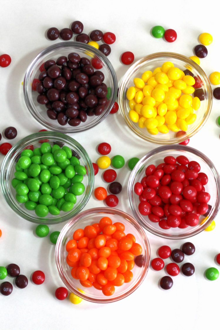 Skittles separated into bowls by flavor and scattered on table
