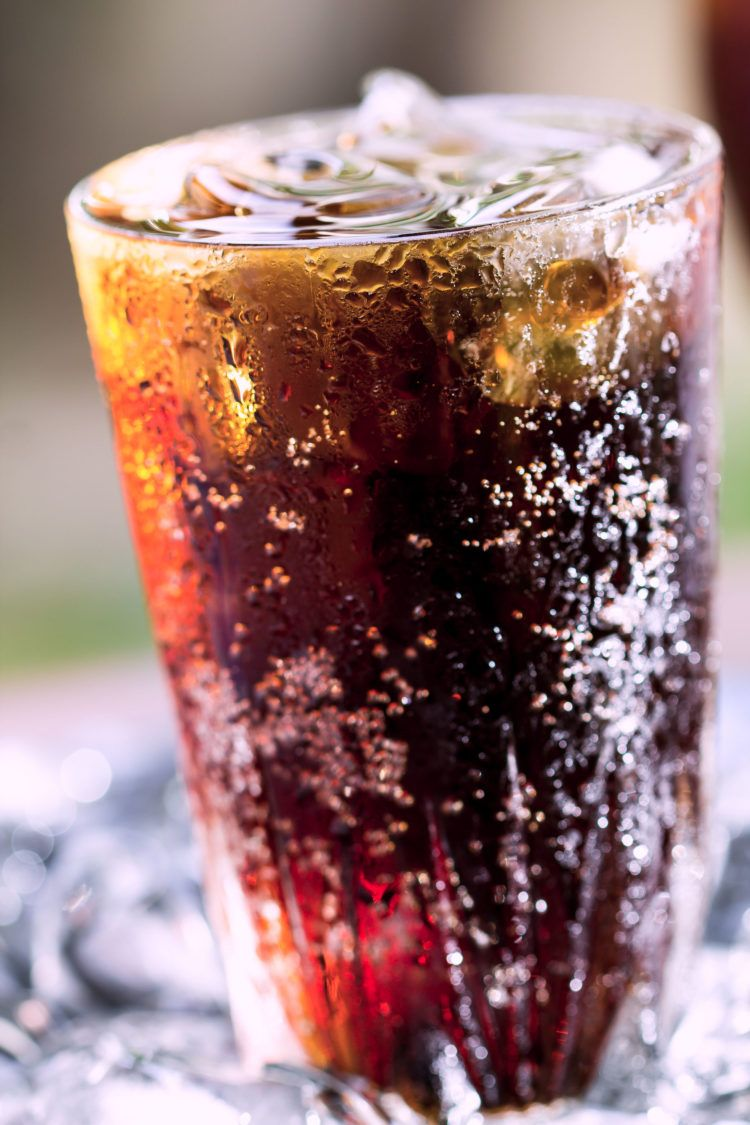 Dark bubbly beverage in tall glass with ice