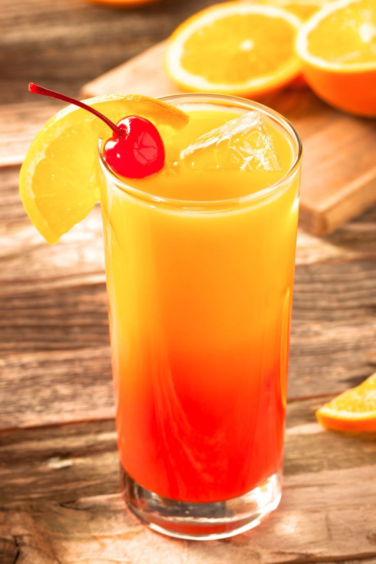 Tequila Sunrise with orange and cherry garnish