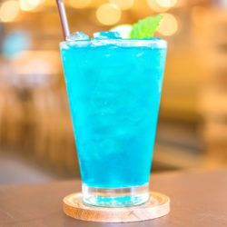 Blue Long Island Iced Tea sitting on coaster on bar